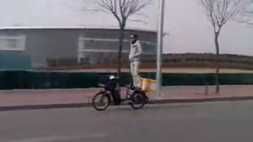 Spotted in Beijing, a food delivery boy with an usual way of riding around town on his electric scooter for deliveries.