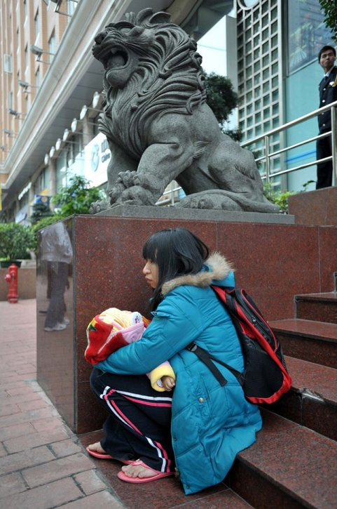 Mother Xie Sanxiu resting on some steps during her mission to crawl 1000m along Guangzhou Avenue in hopes of getting a donation from a wealthy young man online.