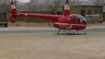 A red helicopter lands on the sports field at Dezhou University in Shandong, to pick up a single female university student.