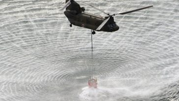 A Japanese Self-Defense Force (SDF) helicopter collects water to dump on the damaged Fukushima I nuclear power plant reactors to bring down reactor temperatures.