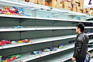 A Chinese man looks at an empty supermarket shelf where most of the laundry detergent has been purchased.