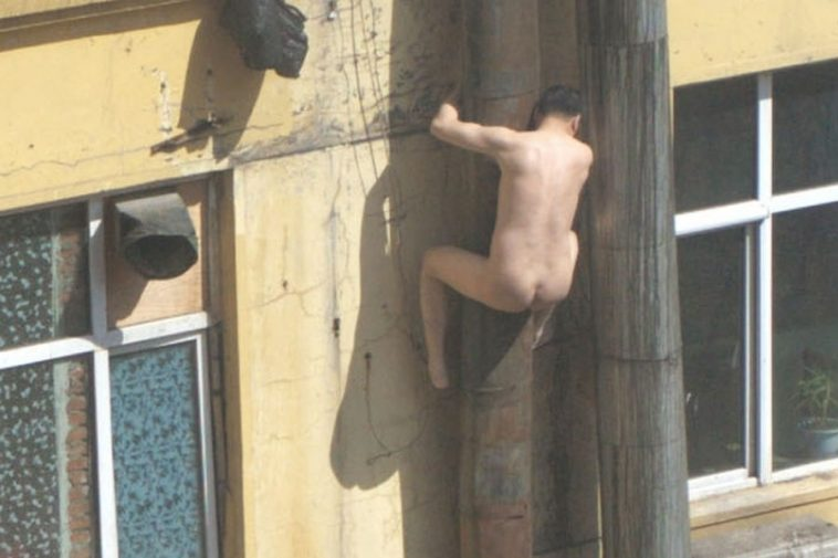 A naked Chinese man trying to climb down the side of a building to flee an anti-prositution police raid in Changchun, China.