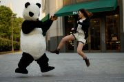 A Chinese girl jump kicking a panda.