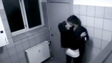 A teenage girl caught on camera forcefully kissing a teenage boy in a restroom.