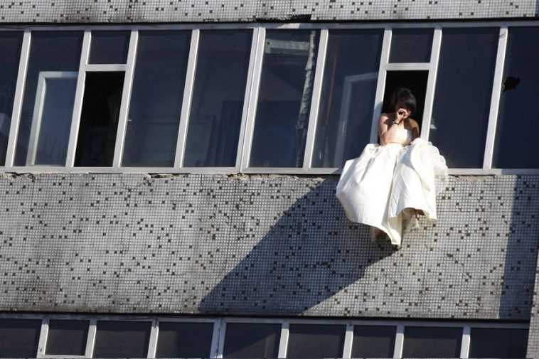 In Changchun, China, a young girl in a wedding dress sits on a window sill 7 floors above the ground.
