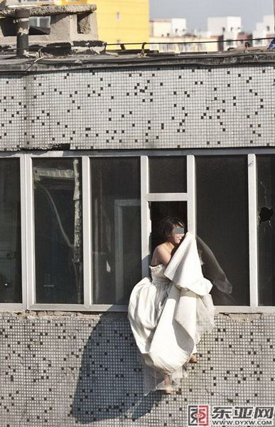 A young Chinese girl in a wedding dress hangs out of a window, distraught, thinking of suicide.