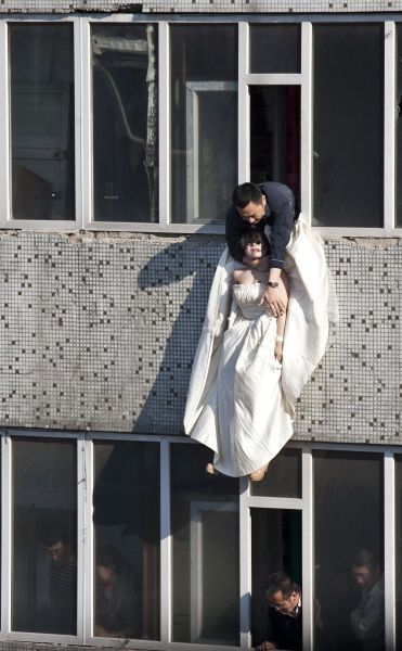 A local government official with his arms around a girl in a wedding dress who had just jumped from the 7th floor.