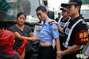 An embarrassed-looking chengguan appears to be under the control of a female peddler during an altercation