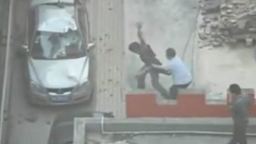 A Chinese man on a roof throwing bricks down onto cars parked below, a security guard tries to stop him.