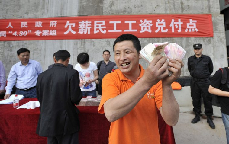 A happy Chinese migrant worker in Chongqing holding up the overdue wages he has finally been paid.