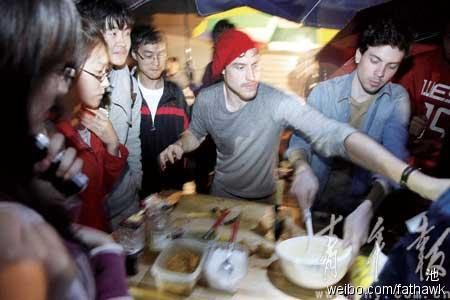 Julien and Benoit, two French students selling crepes to local university students on the street in Shanghai, China.