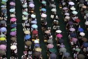 Parents and students under umbrellas in the rain in Guangdong, China.