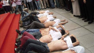 Students lying chest bare on the ground in front of the stage protesting a long boring speech.