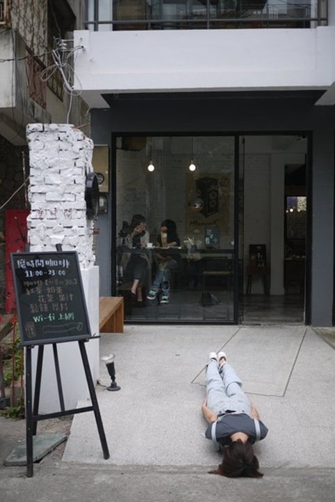 In Taiwan, a girl lies flat on the ground outside a small cafe restaurant.