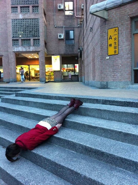 A young girl in Taiwan lies face down over some steps.
