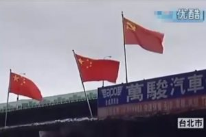 A Taipei, Taiwan resident places People's Republic of China flags in protest of inadequate compensation for eviction from and demolition of his home.