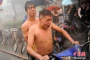 Two topless Beijing residents riding in torrential rains.