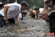 Several male Chinese in Beijing attempt to open a sewer manhole cover.