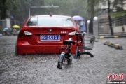 A red BMW 3-series and bicycle half submerged in Beijing flood.