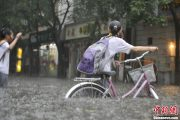 Several Chinese schoolgirls with their bikes in Beijing flood waters.