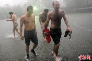 A Chinese and foreigner walking through heavy Beijing rain and flooding.