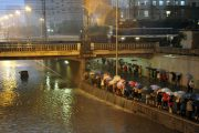 Dozens of Chinese commuters under umbrellas waiting for buses alongside a flooded underpass.
