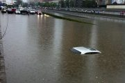 The roof of a submerged car is barely visible as a traffic jam of cars are stopped by a flooded underpass.