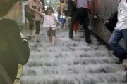 Rainwater cascades down the steps of a Beijing subway station as the city floods from torrential rains.