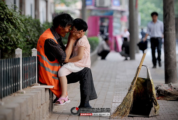 An old Chinese sanitation worker smiles and laughs with his granddaughter on his knees.