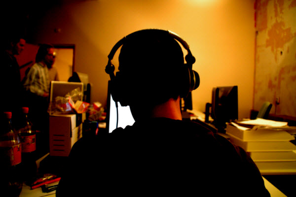 The back of a man wearing headphones at a computer.