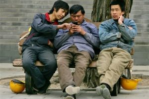 Chinese migrant workers using mobile phones.