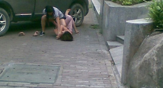 A wive attacks her husband's mistress on the side of a street in Guangzhou, China.