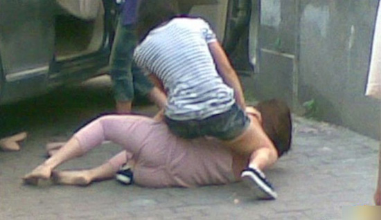 A Chinese wife beating her cheating husband's girlfriend on a street in Guangzhou, China.