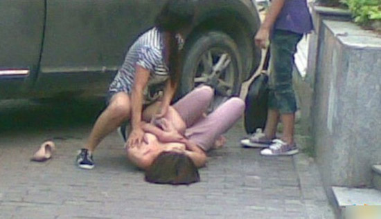 A Chinese wife tears at her cheating husband's girlfriend's clothes on a street in Guangzhou, China.