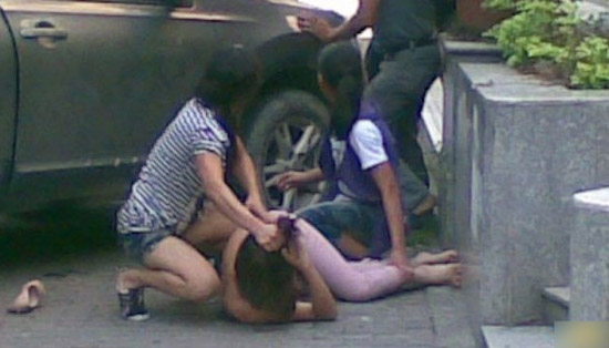 A Chinese wife pulls at her cheating husband's girlfriend's hair on a street in Guangzhou, China.