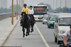 A wealthy Shanxi boss rides a horse to work with his female secretary.