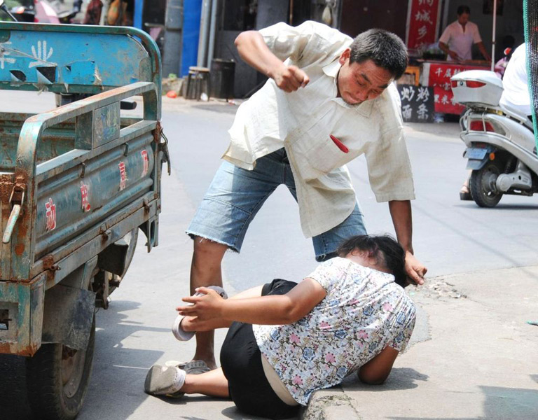 """A migrant worker in Zhejiang province of China beating his wife in public for """"not listening/obeying""""."""