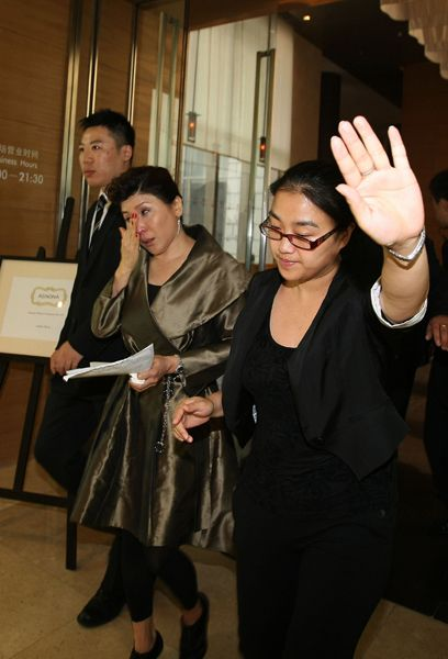 Da Vinci Furniture general manager Panzhuang Xiuhua leaving the press conference under escort, refusing to accept interviews or questions.