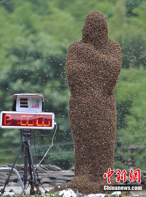 """A Chinese """"beekeeper"""" covered in bees at a competition in Hunan, China."""