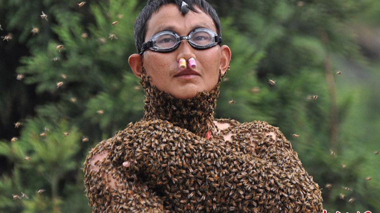 "A 40-year-old Chinese ""beekeeper"" covered in bees at a competition in Hunan, China."