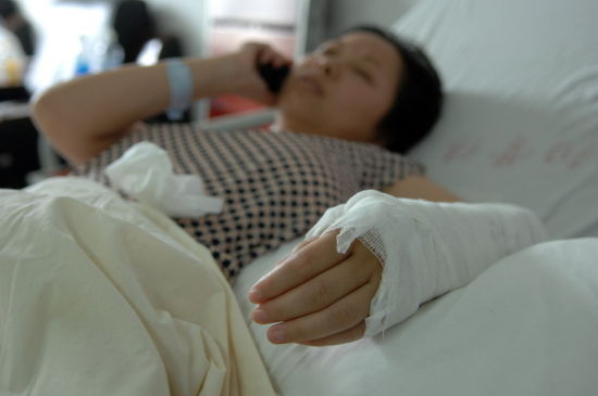 Wu Juping talking on her mobile phone while recovering in the hospital with a broken arm.