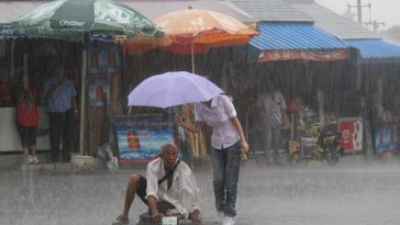 A girl holds an umbrella for a disabled beggar caught in a downpour.