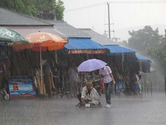 A young Chinese girl holds an umbrella for an old disabled beggar during a rainstorm.
