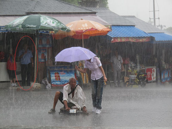 A Chinese girl holds a purple umbrella for a disabled beggar during a rainstorm.