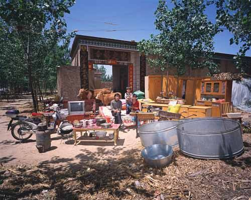 Chinese families in front of their homes with their household possessions.