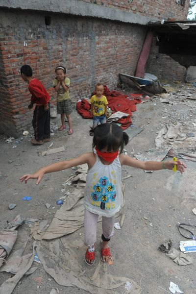 Guiyang migrant worker children playing outside their home next to a garbage landfill.