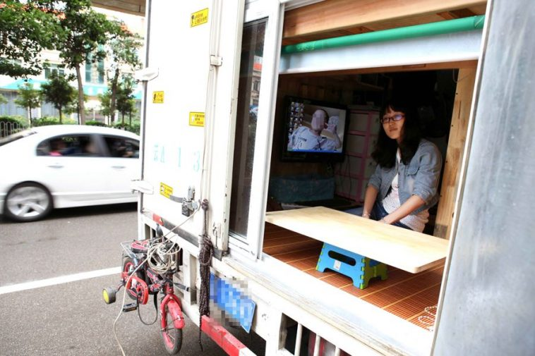 A Chinese woman sits in a cargo truck that has been transformed into a mobile home.