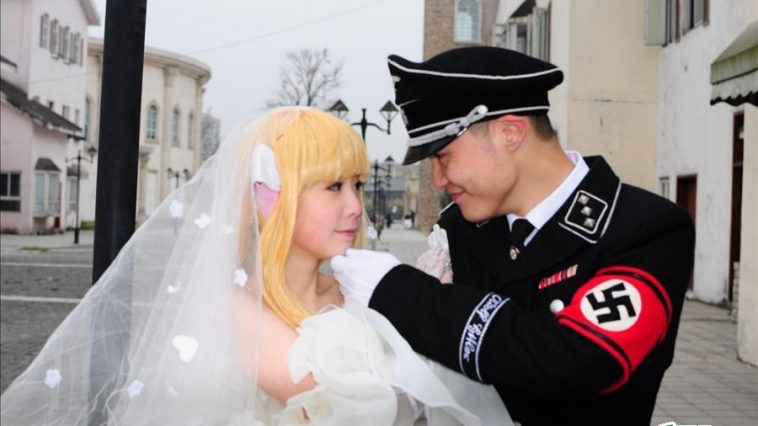 "Cosplay featuring a character dressed in a SS Nazi officer uniform and a character dressed as ""Chi"" from the anime ""Chobits"""