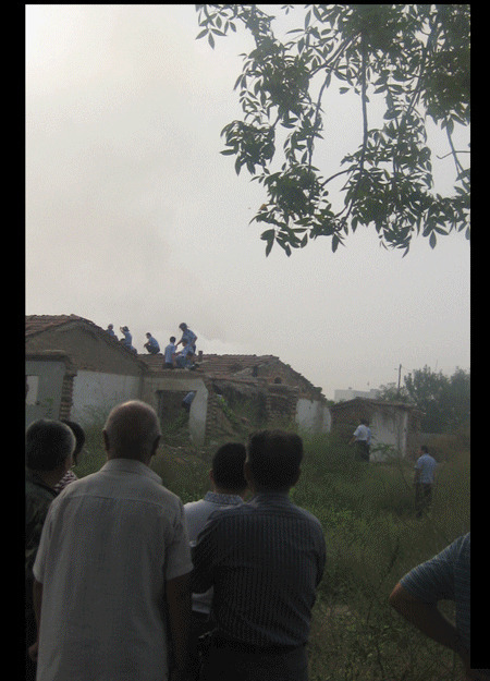 A Chinese couple stand on their roof to protect and protest their home being forcibly demolished.