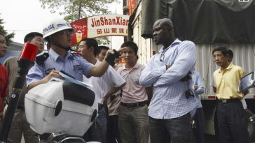 A Guangzhou police officer talking to an African.